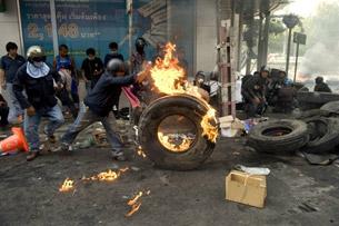 បាតុកររុញកង់ឡានឆេះ ក្នុងអំឡុងពេលប៉ះទង្គិចគ្នាជាមួយកងកម្លាំងសន្តិសុខ នៅក្នុងទីក្រុងបាងកក ប្រទេសថៃ កាលពីថ្ងៃ១៥ ឧសភា ២០១០។ (AFP Photo)