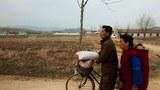 북한의 한 남성이 식량을 실은 자전거를 끌고 가고 있다.