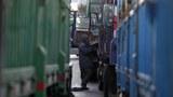 단둥 세관에서 한 중국인 운전수가 북한으로 가는 화물이 가득 실린 트럭들 사이에서 짐을 싣고 있다.