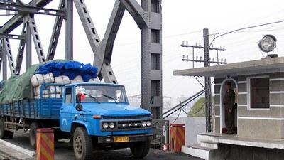 식량을 가득 실은 트럭이 압록강 다리를 지나 북한으로 들어가고 있다.