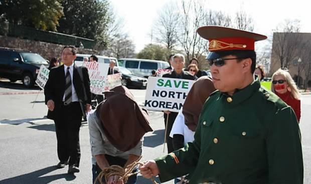 탈북자 강제북송에 항의하는 미국 인권단체들이 지난 2012년 주미 중국 대사관 앞에서 벌인 시위에서 중국 공안 복장을 한 한 참가자가 얼굴을 가린채 포박을 한 여성들을 끌고가고 있다.