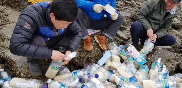 10일 석모도에서 북한 인권 단체 회원들이 페트병에 쌀과 마스크를 넣어 북한에 띄워보내려고 하고 있다.
