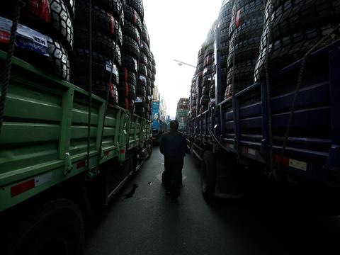 단둥에서 한 운전사가 북한으로 운송할 상품을 실은 트럭 사이로 지나가고 있다.