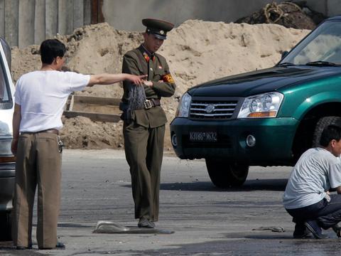북한 신의주 압록강 강둑의 주민들과 군인의 모습.