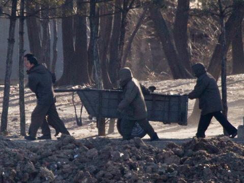 북한 신의주의 강둑에서 주민들이 짐이 담긴 수레를 끌고 있다.