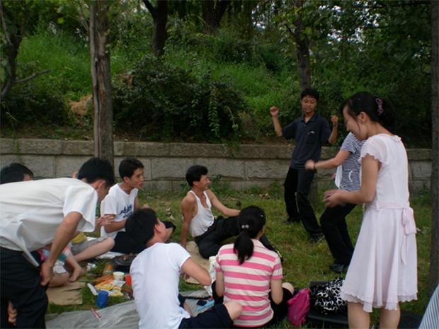 휴일에 풀밭 나무그늘 아래서 친구들과 춤을 추며 즐거운 한 때를 보내고 있는 북한 젊은이들(2011년 8월).