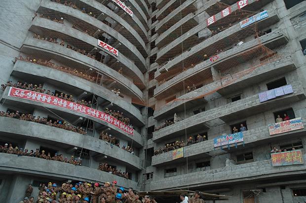 평양시 장전거리 건설현장에서 건설중인 한 고층건물에서 인민군대와 청년돌격대원들이 건설 현장에서 펼쳐진 즉석 공연을 보며 박수치고 있다. (2011년 9월)