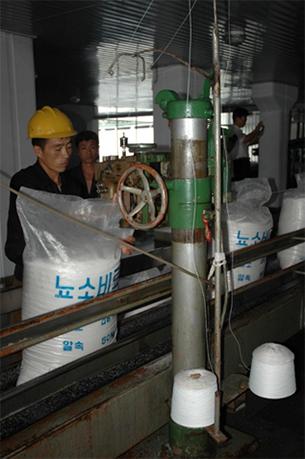 남흥청년화학연합기업소 내 공장에서 생산된 요소비료를 직원들이 비닐 포대에 담아 포장하고 있다.