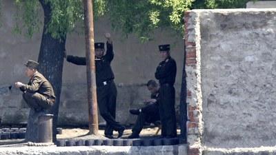 압록강변 나무 그늘 밑에서 북한군 병사들이 휴식을 취하고 있다.