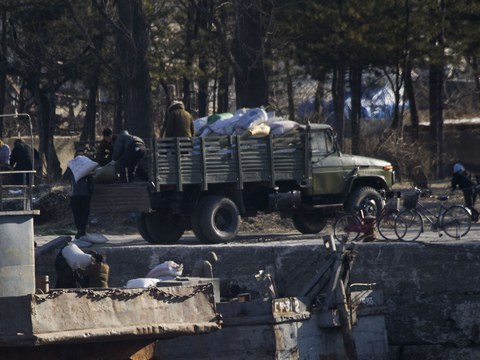 신의주 압록강변에서 북한 사람들이 트럭에 짐을 싣고 있다.