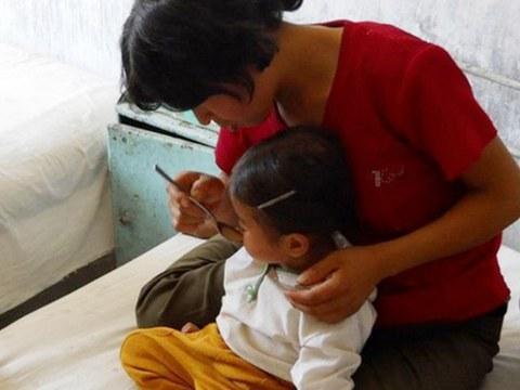 북한 황해북도 한 병원에서 영양실조에 걸린 여자 어린이가 치료식을 먹고 있다.