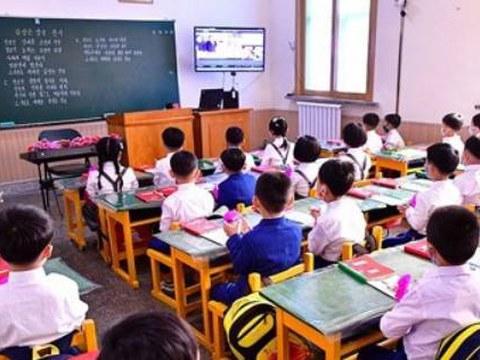 지난해 6월 평양시 대동강구역 옥류소학교에서 개학식이 영상회의체계 '락원' 내부망을 통해 진행된 모습. 교실 안에서도 마스크를 쓴 어린이들이 TV로 개학식을 지켜보고 있다. 교실 칠판에는 '김정은 장군 찬가'가 필기돼 있다.