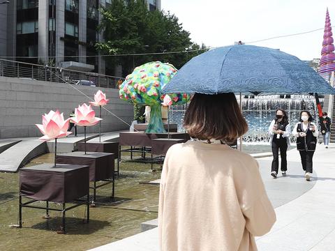 화창한 날씨를 보인 11일 오후 서울 청계천을 찾은 시민이 양산을 쓰고 이동하고 있다.
