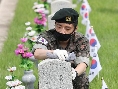 한국전쟁 발발 71주년을 맞은 25일 동작구 국립서울현충원에서 한 부대 장병이 묘역정리를 하고 있다.