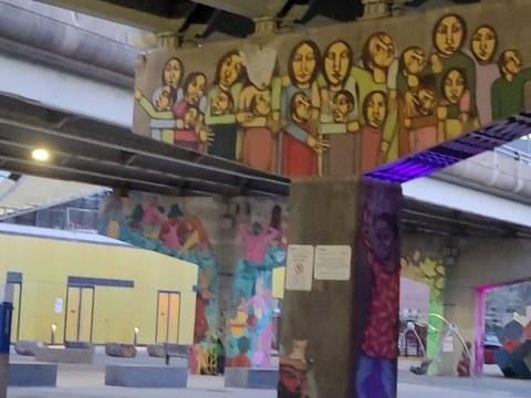 다리기둥 전체가 그래피티로 채워진 철교밑 공터에서 아이들이 운동하고 있다.