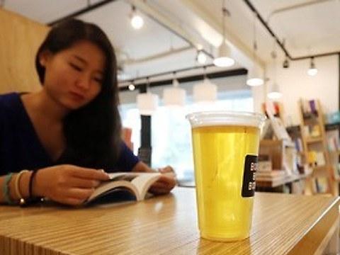 퇴근길 직장인이 맥주 한잔을 기울이며 책을 읽고 있다.