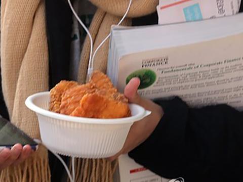 이화여자대학교 학생회관 앞에 한 학생이 무료 치킨을 받고 있다.
