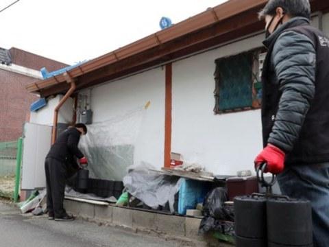 강원 춘천시 효자동의 한 골목에서 이웃에게 연탄을 전하는 춘천연탄은행 직원이 작업을 하고 있다.