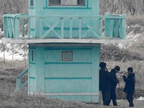 중국 랴오닝성 단둥 외곽에서 바라본 북한지역에서 북한 주민들이 담배를 피고 있다.