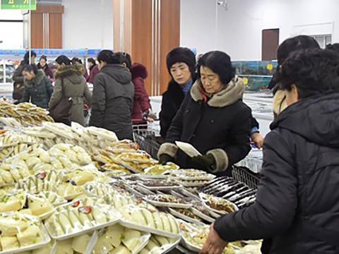 평양의 대형마트 '광복지구상업중심'은 직장 일로 바쁜 여성들을 위해 '아침저녁 매대 봉사'를 진행하고 있다. 사진은 가공 음식을 고르고 있는 북한 여성들의 모습.