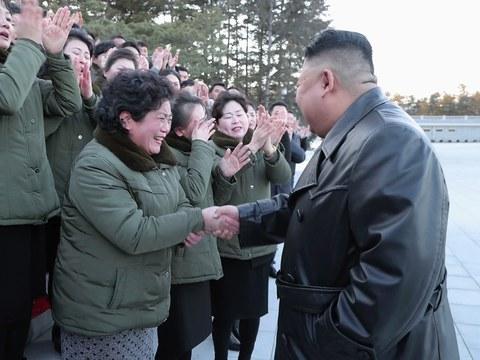 북한 김정은 국무위원장이 근로자들의 손을 잡으며 당대회 준비 노고를 격려하는 모습.