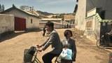 대학생복을 입은 두 남녀가 자전거에 나란히 타고 농촌길을 달리고 있는 모습.