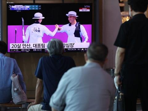 지난 24일 오후 서울역 대합실에서 시민들이 2020 도쿄올림픽 양궁 혼선 결승전에서 금메달을 차지하는 모습을 시청하고 있다.