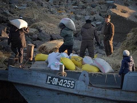 압록강변 북한 국경경비대원들이 배에서 짐을 내리는 주민들을 지켜보고 있다.