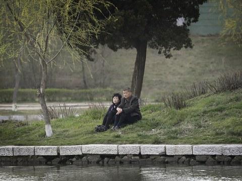 평양 보통강변에서 한 커플이 나란히 앉아 있다.