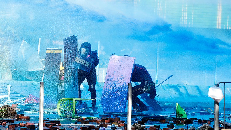 2019年11月17日,香港理工大学的一辆装甲警车上喷出了染成蓝色的液体,抗议者躲在盾牌后面。(美联社)
