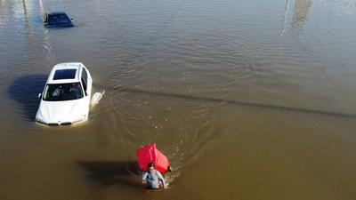 2021 年 7 月 24 日,河南省新乡市的一村庄发生暴雨后,一名男子携带垃圾箱涉水穿过洪水。
