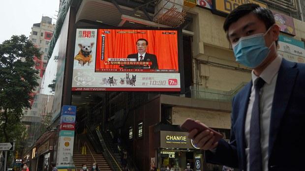 2021年3月5日,电视屏幕在香港播出中国全国人民代表大会(NPC)开幕式的新闻。