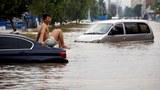 2021 年 7 月 22 日,河南省鄭州市暴雨過後,一名男子坐在被洪水滯留車輛上。