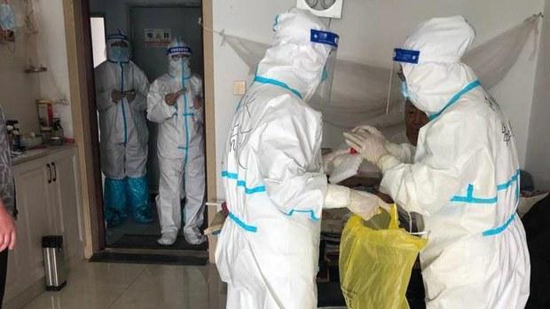 穿防护服的人员正在给居民做核酸检测。(志愿者提供)