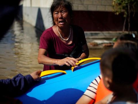 2021 年 7 月 24 日,河南省新乡市的一村庄遭遇暴雨,村民站在洪水中请求救援人员帮助她的家人。