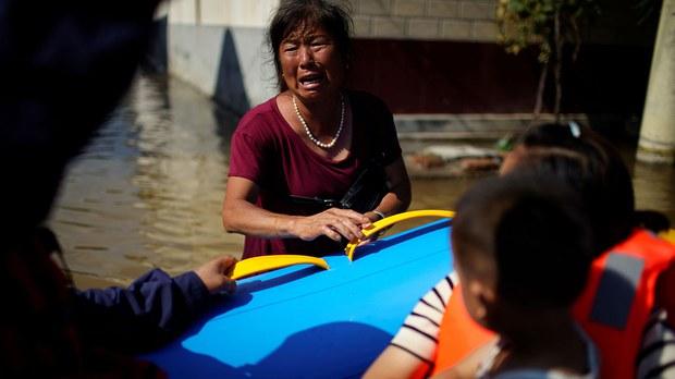 2021 年 7 月 24 日,河南省新鄉市的一村莊遭遇暴雨,村民站在洪水中請求救援人員幫助她的家人。