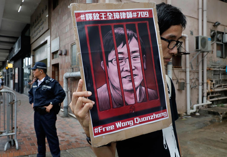 """2018年7月13日,中国政府驻香港联络处中联办外,一名示威者拿着""""释放王全璋""""的图片。(AP)"""