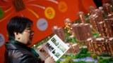 圖爲,上海房地產展覽期間,一名婦女參觀了房地產攤位。