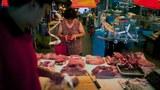 北京一市場,一名婦女在錢包裏找現金來購買豬肉。