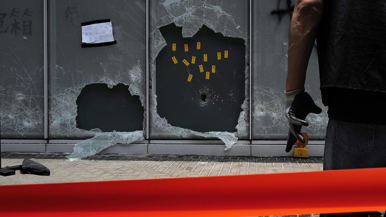 一名香港警察站在香港立法会外的破损的玻璃旁边。(美联社)