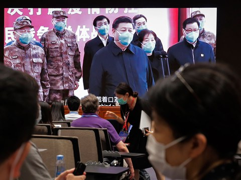 2020年6月7日,记者在屏幕旁,屏幕上显示习近平主席通过视频在湖北省武汉火神山医院指挥中心与患者和医务人员进行视频对话,然后在国务院新闻办公室发布《抗击新冠肺炎疫情的中国行动》白皮书并举行新闻发布会。