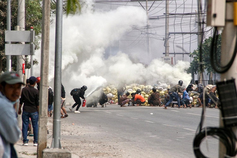 在Mandalay城市,示威者躲在路障后方。(图源:路透)