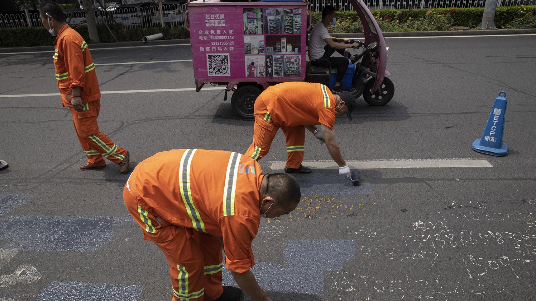 2020年7月31日,北京的工人在清理地上的广告涂鸦。(美联社)