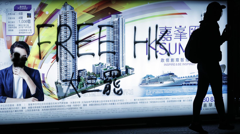 """2019年12月8日,一名香港抗议者走过写有""""解放香港""""等标语的广告牌。(美联社)"""
