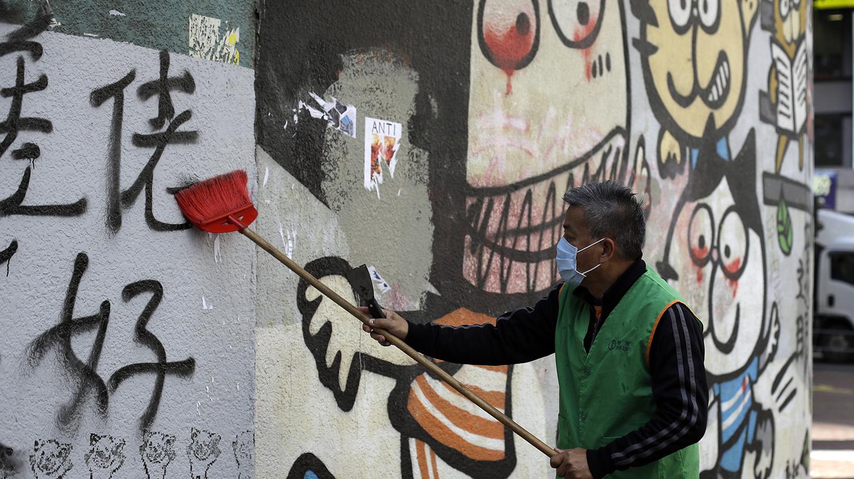 2019年12月9日清洁工人在清理香港街头的标语和涂鸦。(美联社)