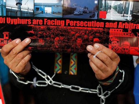 资料图片:一名维吾尔族示威者抗议中国新疆政策。