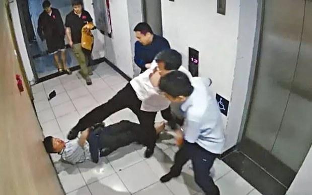 王晋年被殴打倒地,旁人赶忙将张陶拦下。