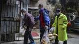 2020年3月16日,武汉的一些志愿者在帮助一个老人领取蔬菜。(法新社)