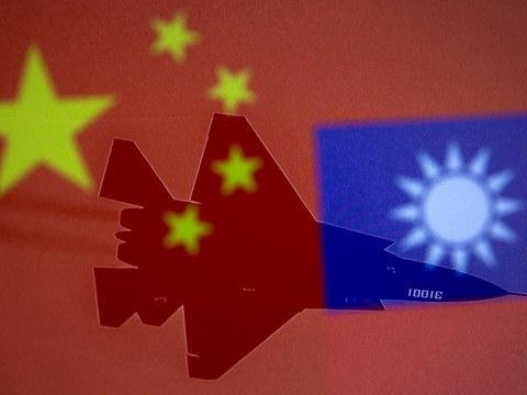 圖爲,中國和臺灣的旗幟與一架軍用飛機並排展示。