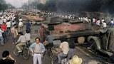 1989年6月4日清晨,解放军进入天安门广场镇压学生后,一辆已被焚烧的坦克遗留在街道上。(AFP)